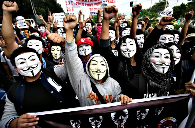Filipino student protesters wearing masks raise their clenched f