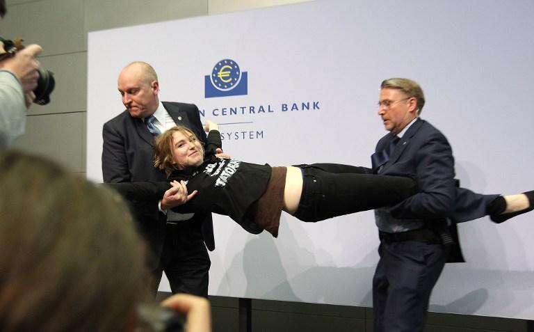 """Konferencija za medije predsjednika Europske središnje banke (ESB) Marija Draghija prekinuta je kad je na stol ispred njega skočila prosvjednica uzvikujući """"Zaustavimo diktaturu Europske središnje banke"""" AFP PHOTO / DANIEL ROLAND"""