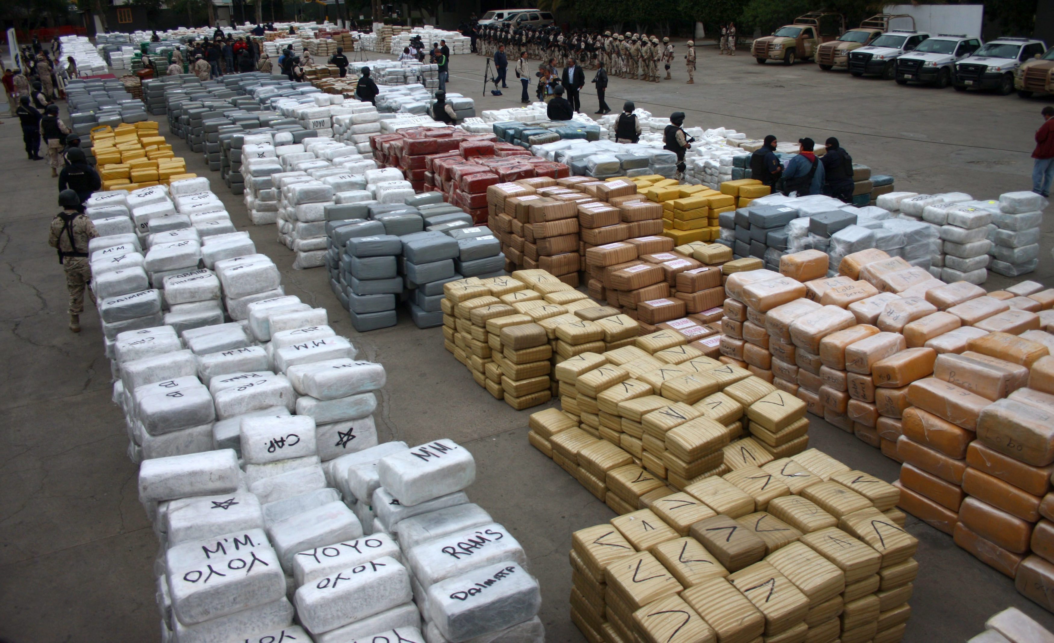 Narcotics wrapped in 10,000 brown and silver packages are on display in the patio of the Morelos military base in Tijuana October 18, 2010. Mexican soldiers seized 105 tonnes of marijuana with a U.S. street value of more than $340 million on Monday in Mexico's biggest-ever pot haul, the army said. Heavily armed soldiers raided a series of homes in a poor suburb of Tijuana, across the border from San Diego, California, and came under fire at least once as they took the drugs, also arresting 11 suspected traffickers.  REUTERS/Jorge Duenes (MEXICO - Tags: POLITICS CRIME LAW SOCIETY IMAGES OF THE DAY) - RTXTKOZ