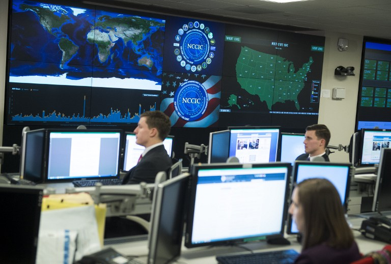 Staff members sit at their work stations at the National Cybersecurity and Communications Integration Center in Arlington, Virginia, January 13, 2015. US President Barack Obama visited the facility to talk about cyber security. AFP PHOTO / SAUL LOEB