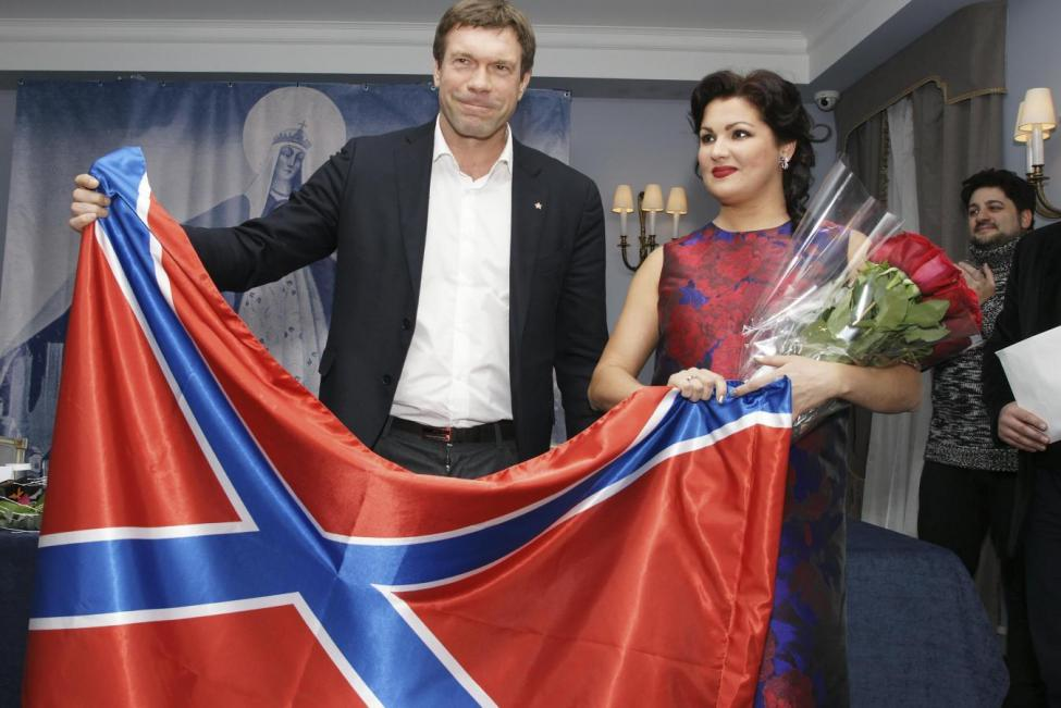 Opera singer Anna Netrebko (R) and Oleg Tsaryov, former deputy of the Ukrainian parliament and pro-Russian politician, hold up a flag of Novorossiya (New Russia) during a charitable ceremony and news conference in St. Petersburg, December 7, 2014.  REUTERS/Stringer