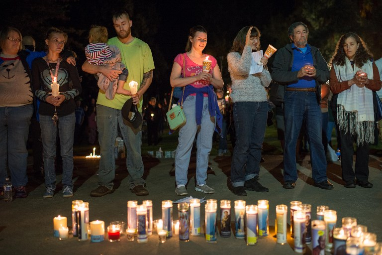 People pray during a candlelight vigil in Roseburg, Oregon late on October 1, 2015, for ten people killed and seven others wounded in a shooting at a community college in the western US state of Oregon. The shooter -- identified by US media as Chris Harper Mercer, 26 -- opened fire in a classroom at Umpqua Community College in rural Roseburg, then moved to other rooms methodically gunning down his victims, witnesses said. AFP PHOTO / Cengiz Yar Jr.
