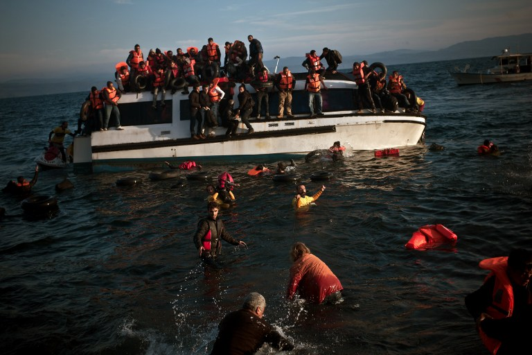 Refugees and migrants react as their boat sinks off the Greek island of Lesbos after crossing the Aegean sea from Turkey on October 30, 2015. AFP PHOTO / ANGELOS CHRISTOFILOPOULOS
