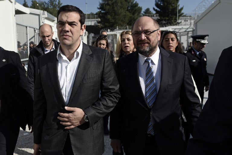 Greek Prime Minister Alexis Tsipras (L) and European parliament President Martin Schulz visit the Moria Hot Spot in Mytilene on November 5, 2015. Since the start of the summer, the Greek island of Lesbos has assumed notoriety as the main gateway into Europe for thousands of desperate refugees. AFP PHOTO / ARIS MESSINIS