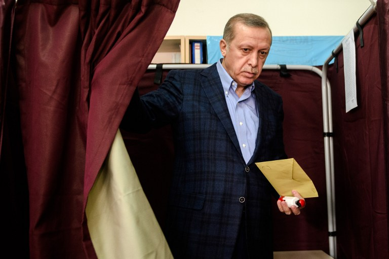 TOPSHOTS Turkish President Recep Tayyip Erdogan exits a voting booth at a polling station in Istanbul on November 1, 2015. Turkey voted November 1 in one of its most crucial elections in years, with the country deeply divided in the face of surging Kurdish and Islamic violence and concerns about democracy and the economy. The poll is the second in just five months, called after President Recep Tayyip Erdogan's Justice and Development Party (AKP) was stripped of its parliamentary majority in June for the first time in 13 years and then failed to forge a coalition government. AFP PHOTO / OZAN KOSE