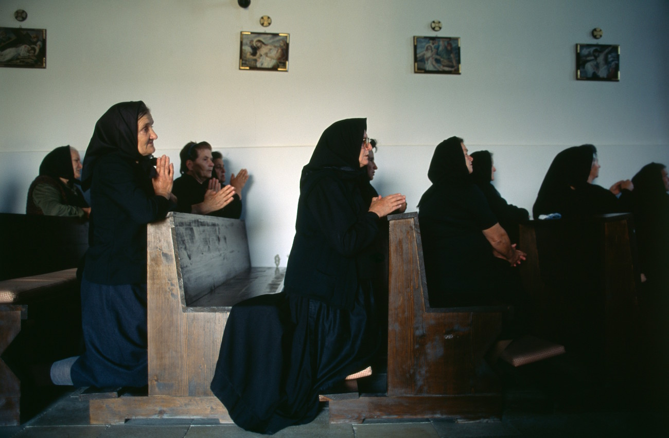 Mourners pray during the funeral of a Croat woman killed in the battles against Serbs during the Yugoslavian Civil War in the small Croatian village of Novi Mikanovci, located 50km from Vukovar., Image: 15113462, License: Rights-managed, Restrictions: Content available for editorial use, pre-approval required for all other uses. This content may not be materially modified or used in composite content., Model Release: no, Credit line: Profimedia, Corbis