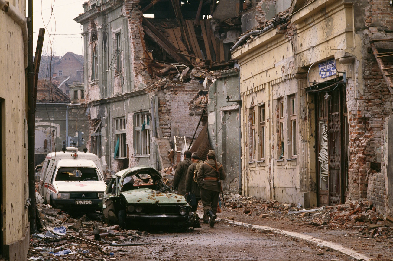 "Yugoslavian soldiers and Serb paramilitaries, including Zeljko ""Arkan"" Raznatovic, walk past bombed buildings riddled with bullet holes and streets filled with rubble after a three-month battle between the Croatian armed forces and the Yugoslavian Federal Army in Vukovar. The Yugoslavian Federal Army completely destroyed the Croatian city, killing thousands of civilians, while the Serbian Volunteer Guard, formed by Raznatovic, was responsible for massive ethnic cleansing campaigns against Bosnian Croats., Image: 15114608, License: Rights-managed, Restrictions: Content available for editorial use, pre-approval required for all other uses. This content may not be materially modified or used in composite content., Model Release: no, Credit line: Profimedia, Corbis"