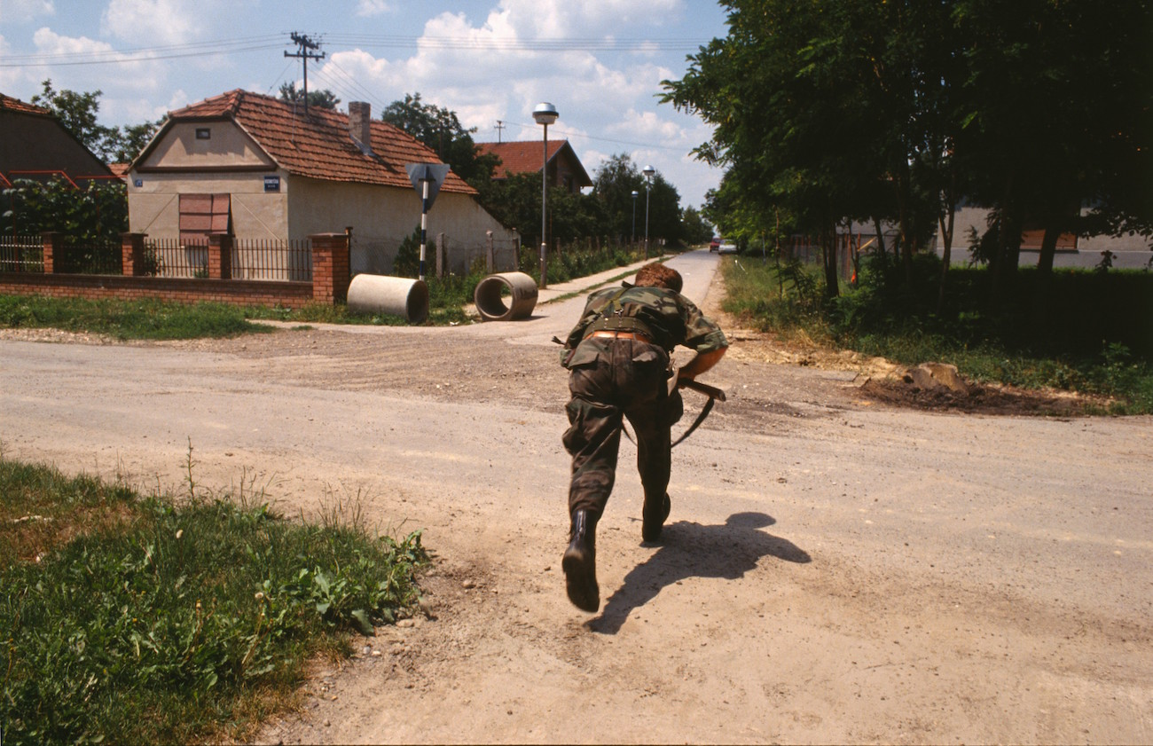 A Croatian soldier runs across the road in the suburbs of Vukovar., Image: 17623486, License: Rights-managed, Restrictions: Content available for editorial use, pre-approval required for all other uses. This content may not be materially modified or used in composite content., Model Release: no, Credit line: Profimedia, Corbis