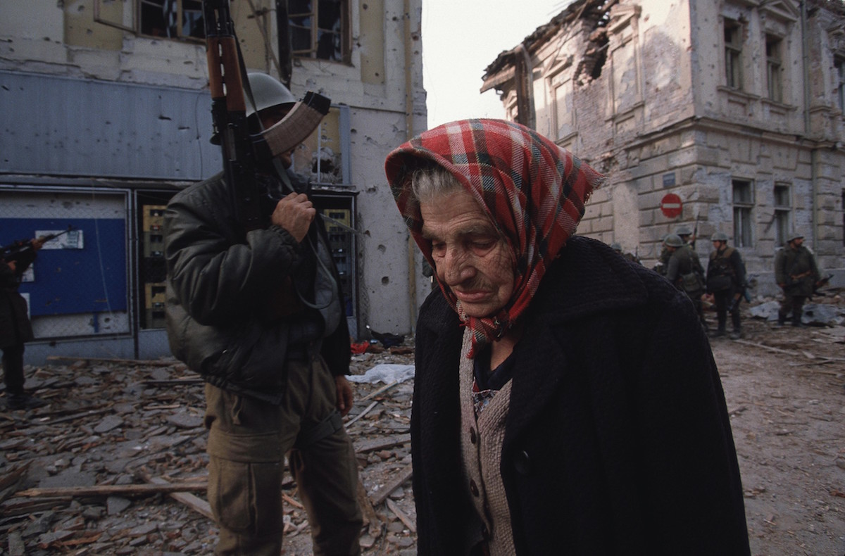 Ethnic Cleansing - A Croatian woman walks past a Serbian fighter as she leaves her destroyed city of Vukovar, Croatia, Nov. 24, 1991. Vukovar was under siege for three months by Serbian forces and completely destroyed., Image: 116177610, License: Rights-managed, Restrictions: Content available for editorial use, pre-approval required for all other uses. This content not available to be downloaded through Quick Pic Not available for license and invoicing to customers located in the Czech Republic. Not available for license and invoicing to customers located in the Netherlands. Not available for license and invoicing to customers located in India. Not available for license and invoicing to customers located in Italy. Not available for license and invoicing to customers located in Finland., Model Release: no, Credit line: Profimedia, Corbis VII