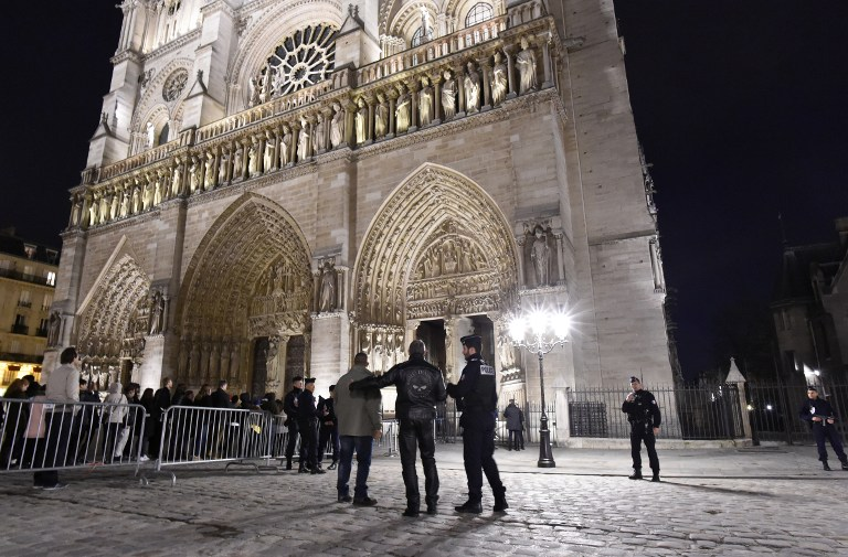 French Police officers stand guard outside the Cathedral of Notre Dame de Paris as people queue to attend a mass on December 25, 2015, in Paris.  AFP PHOTO / MIGUEL MEDINA / AFP / MIGUEL MEDINA