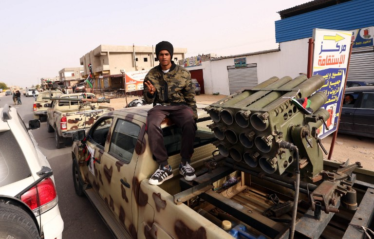 A Member of a brigade loyal to the Fajr Libya (Libya Dawn), an alliance of Islamist-backed fighters, gestures to the camera as he sits on a pick up truck mounted with a multiple rocket launcher during a military parade following battles against the Islamic State (IS) group, in the city of Sabratha, west of the capital Tripoli, on February 28, 2016. On February 19, a US air strike near Sabratha targeted a suspected IS training camp, killing 50 people. / AFP / MAHMUD TURKIA
