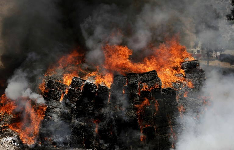 View of forty tons of marijuana seized to alleged drug cartels in a house of the bordering city of Tijuana, Baja California, Mexico being burned by the Mexican Army at their training camp in El Aguaje de La Tuna, Tijuana, Mexico on May 16, 2014. According to the Interior Ministry, this is the largest seizure of marijuana so far this administration. AFP PHOTO/Alonso ROCHIN / AFP / ALONSO ROCHIN