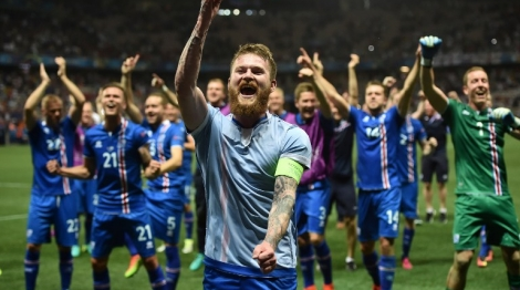 Iceland's midfielder Aron Gunnarsson and team mates celebrate after the Euro 2016 round of 16 football match between England and Iceland at the Allianz Riviera stadium in Nice on June 27, 2016.   Iceland won the match 1-2. / AFP PHOTO / BERTRAND LANGLOIS