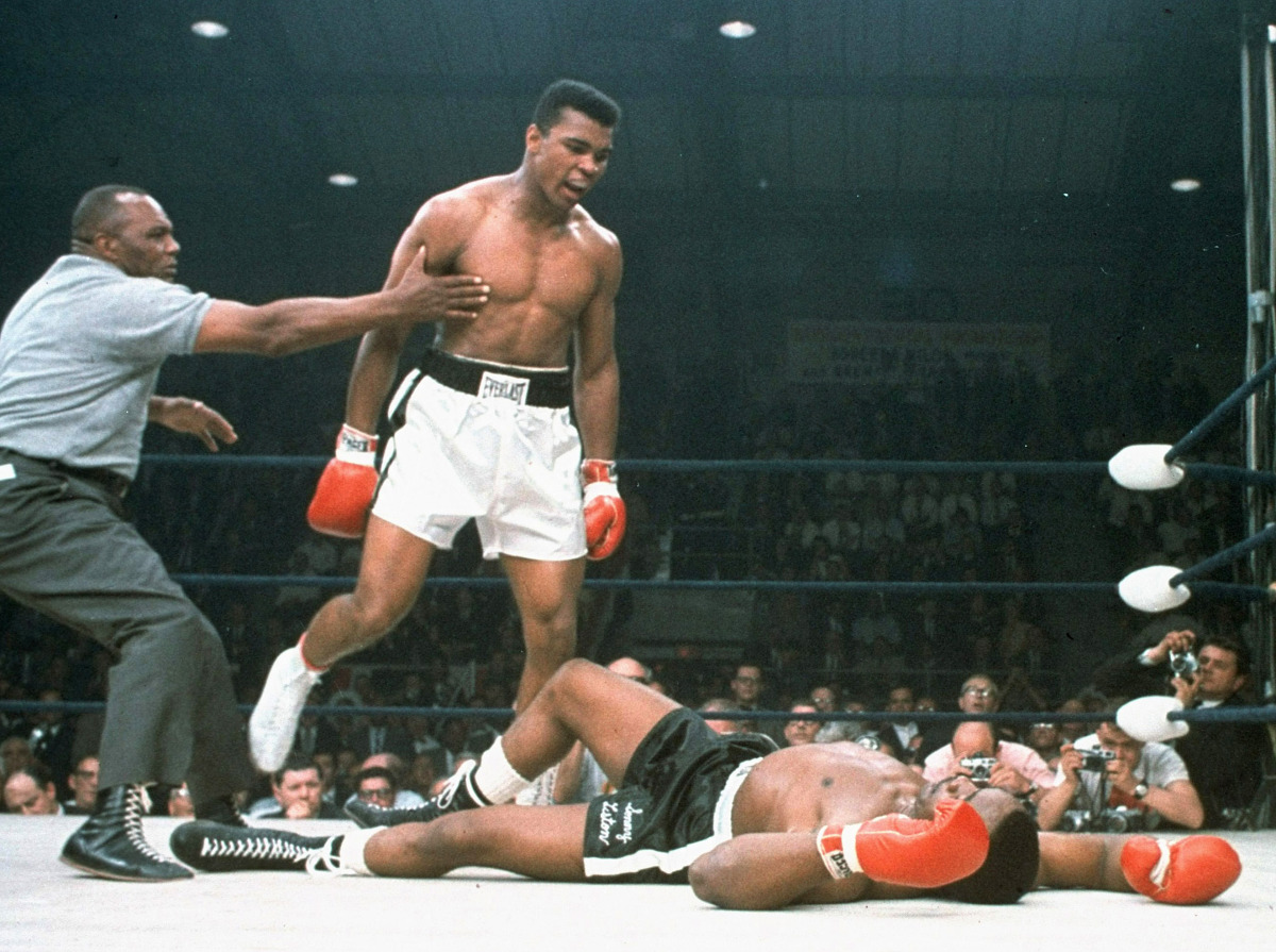 FILE - In this May 25, 1965 file photo, heavyweight champion Muhammad Ali is held back by referee Joe Walcott after Ali dropped challenger Sonny Liston less than two minutes into the first round of their heavyweight title fight, in Lewiston, Maine. Just months before the 50th anniversary of the fight, which remains one of the most controversial sporting events of the 20th century, both pairs of gloves are going on the auction block for the first time. Heritage Auctions is offering them as a single lot on Feb. 21 in New York. The auctioneer expects they will sell for more than $1 million. Bidding will start at $500,000. (AP Photo/File)