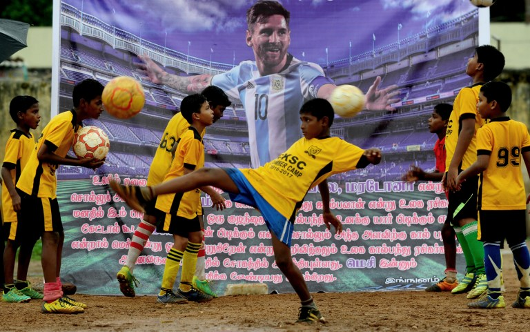Indian youths play football in front of a poster of Argentinian footballer, Lionel Messi displayed at a football ground and saying that Messi should come back, in Chennai on June 29, 2016. Argentina was defeated in the Copa America final against Chile, 4-2, in a penalty shoot-out. Argentinians begged Lionel Messi - who tearfully decided to quit the international team after missing a spot-kick in the shootout - not to leave the national team despite its traumatic final. / AFP PHOTO / ARUN SANKAR
