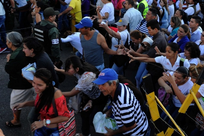 Venezuelans cross from San Antonio del Tachira, Venezuela to Cucuta, Colombia on July 10, 2016. Thousands of Venezuelans crossed Sunday the border with Colombia to take advantage of its 12-hour opening after it was closed by the Venezuelan government 11 months ago. Venezuelans rushed to Cucuta to buy food and medicines which are scarce in their country. / AFP PHOTO / GEORGE CASTELLANOS