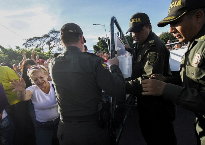 Colombian (R) and Venezuelan (L) policemen lift the fence to open the border as Venezuelans cross the Simon Bolivar bridge from San Antonio del Tachira, Venezuela to Cucuta, Colombia on July 10, 2016. Thousands of Venezuelans crossed Sunday the border with Colombia to take advantage of its 12-hour opening after it was closed by the Venezuelan government 11 months ago. Venezuelans rushed to Cucuta to buy food and medicines which are scarce in their country. / AFP PHOTO / Schneyder Mendoza