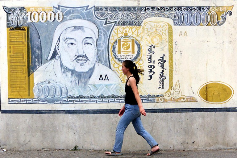 A young Ulan Bator woman walks 30 June 2000 by a large 10,000 Mongolian banknote, called the togrog and roughly equivalent to 10 USD, painted on the wall of a delapidated warehouse. The Asian Development Bank estimates 36 percent of Mongolians live in poverty, and widespread unemployment and social deprivation is a key election issue in the coming 02 July Mongolian government elections. (ELECTRONIC IMAGE) AFP PHOTO/Stephen SHAVER / AFP PHOTO / STEPHEN SHAVER