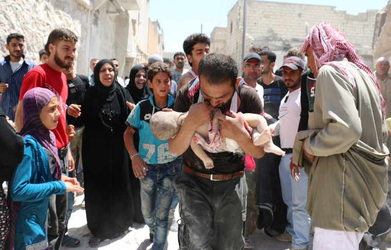 A Syrian man holds the body of his child after it was taken from under the rubble of destroyed buildings following a reported air strike on the rebel-held neighbourhood of al-Marjah in the northern city of Aleppo, on July 24, 2016. Air raids have hit four makeshift hospitals in Syria's battered Aleppo city, doctors said, jeopardising medical care for more than 200,000 desperate civilians in rebel-held areas. The bombardment since July 23 has worsened the plight of residents of besieged eastern neighbourhoods of Syria's second city, where food and medical supplies are becoming increasingly scarce. / AFP PHOTO / AMEER ALHALBI