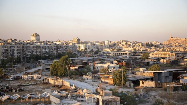 A picture taken on July 29, 2016 shows a general view of Karaj al-Hajz corridor (C) in the rebel-held part of Aleppo, leading towards the government controlled area of the Masharqa neighbourhood (background). Only a few residents of Syria's Aleppo were able to leave encircled opposition-held districts through humanitarian corridors before rebels prevented them from fleeing, the Syrian Observatory for Human Rights said on July 28, adding that Russia, a key ally of President Bashar al-Assad, on July 27 announced the opening of aid passages for civilians and surrendering fighters seeking to exit the city's rebel-held eastern neighbourhoods but regime aircraft bombed eastern areas of Aleppo overnight. / AFP PHOTO / KARAM AL-MASRI