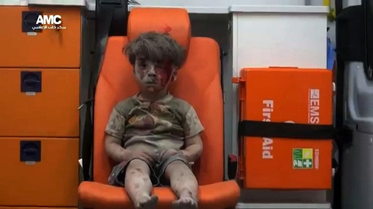 "An image grab taken from a video uploaded by the Syrian opposition's activist group Aleppo Media Centre (AMC) on August 17, 2016 is said to show Omran, a four-year-old Syrian boy covered in dust and blood, in an ambulance after being rescued from the rubble of a building hit by an air strike in the rebel-held Qaterji neighbourhood of the northern Syrian city of Aleppo. / AFP PHOTO / AMC / HO / === RESTRICTED TO EDITORIAL USE - MANDATORY CREDIT ""AFP PHOTO / HO / AMC "" - NO MARKETING NO ADVERTISING CAMPAIGNS - DISTRIBUTED AS A SERVICE TO CLIENTS FROM ALTERNATIVE SOURCES, AFP IS NOT RESPONSIBLE FOR ANY DIGITAL ALTERATIONS TO THE PICTURE'S EDITORIAL CONTENT, DATE AND LOCATION WHICH CANNOT BE INDEPENDENTLY VERIFIED === /"