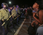 Protesters face off with police in El Cajon, a suburb of San Diego, California on September 28, 2016, in response to a police shooting the night before of Ugandan refugee Alfred Olango. Protesters marched in a California town following the fatal police shooting of an unarmed black man said to be mentally ill, as local officials urged calm and pledged a full investigation.  / AFP PHOTO / Bill Wechter