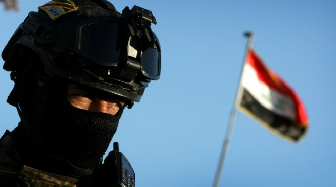 An Iraqi soldier stands guard at the entrance of the Nineveh base for liberation operations in Makhmur, about 280 kilometres (175 miles) north of the capital Baghdad, on February 11, 2016.   The Iraqi army is deploying thousands of soldiers to a northern base in preparation for operations to retake the Islamic State (IS) group's hub of Mosul, according to officials, as IS still holds Fallujah, east of Ramadi, and Mosul, Iraq's second city that is located in the north. / AFP PHOTO / SAFIN HAMED