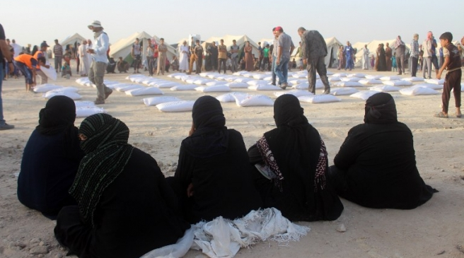 Iraqi women displaced from Ramadi, sit and wait to receive aid from the International Committee of the Red Cross (ICRC) at a makeshift camp where they are taking shelter in Habbaniyah, just east of the capital of Iraq's Anbar province on June 23, 2016.  Iraqi government forces retook control of the city of Ramadi from the Islamic State (IS) group in February 2016 but sporadic IS attacks there have continued.  / AFP PHOTO / MOADH AL-DULAIMI