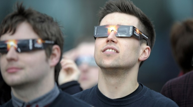 A young man wears protective glasses to view the partial solar eclipse at the Glasgow Science Centre in Glasgow, Scotland on March 20, 2015. AFP PHOTO / ANDY BUCHANAN / AFP PHOTO / Andy Buchanan