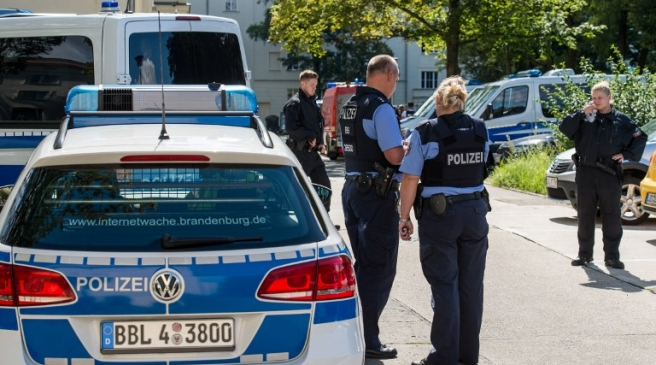 Police officers stand in front of an apartment building in Eisenhuettenstadt, eastern Germany, on August 17, 2016. German police has arrested a 27-year old man who is suspected of having planned an explosives attack on a street festival, local authorities said. / AFP PHOTO / dpa / Patrick Pleul / Germany OUT