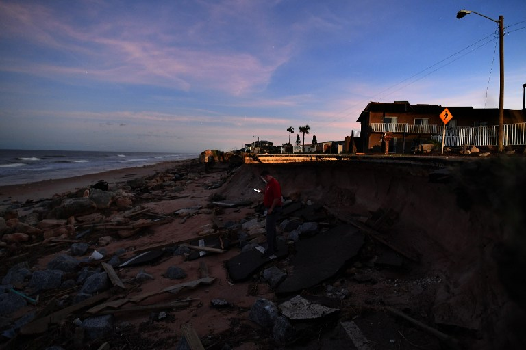 A reporter walks on the debris of a washed out highway in Flagler Beach, Florida, on October 8, 2016, after Hurricane Matthew passed the area. Hurricane Matthew weakened to a Category 1 storm Saturday as it neared the end of a four-day rampage that left a trail of death and destruction across the Caribbean and up the US Atlantic coast. The full scale of the devastation in hurricane-hit rural Haiti became clear as the death toll surged past 400, three days after Hurricane Matthew leveled huge swaths of the country's south. / AFP PHOTO / Jewel SAMAD
