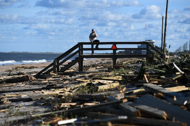 A man leans on a damaged boardwalk at a debris covered beach in St Augustine, Florida, on October 8, 2016, after Hurricane Matthew passed the area. Hurricane Matthew weakened to a Category 1 storm Saturday as it neared the end of a four-day rampage that left a trail of death and destruction across the Caribbean and up the US Atlantic coast. The full scale of the devastation in hurricane-hit rural Haiti became clear as the death toll surged past 400, three days after Hurricane Matthew leveled huge swaths of the country's south. / AFP PHOTO / Jewel SAMAD
