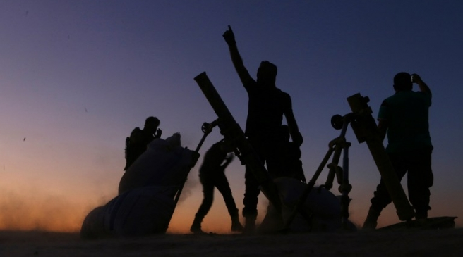 Fighters from the Free Syrian Army cheer and react as they fight against the Islamic State (IS) group jihadists on the outskirts of the northern Syrian town of Dabiq, on October 15, 2016. Turkish-backed fighters were advancing on the northern Syrian town of Dabiq, which has become a rallying cry for the Islamic State group as the prophesied scene of an end-of-days battle. Dabiq holds crucial ideological importance for IS because of a Sunni prophecy that states it will be the site of an end-of-times battle between Christian forces and Muslims.   / AFP PHOTO / Nazeer al-Khatib / ALTERNATIVE CROP