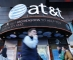 People walk past an AT&T store in New York on October 23, 2016.  AT&T unveiled a mega-deal for Time Warner that would transform the telecom giant into a media-entertainment powerhouse positioned for a sector facing major technology changes. The stock-and-cash deal is valued at $108.7 billion including debt, and gives a value of $84.5 billion to Time Warner -- a major name in the sector that includes the Warner Bros. studios in Hollywood and an array of TV assets such as HBO and CNN. / AFP PHOTO / KENA BETANCUR