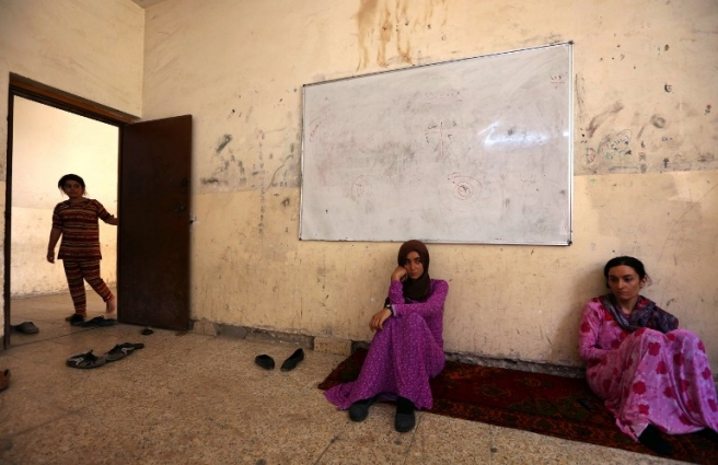 "Iraqi Yazidi women who fled the violence in the northern Iraqi town of Sinjar, sit at a school where they are taking shelter in the Kurdish city of Dohuk in Iraq's autonomous Kurdistan region, on August 5, 2014. Islamic State (IS) Sunni jihadists ousted the Peshmerga troops of Iraq's Kurdish government from the northern Iraqi town of Sinjar, forcing thousands of people from their homes. The Yazidis, are a small community that follows a 4,000-year-old faith and have been repeatedly targeted by jihadists who call them ""devil-worshipers"" because of their unique beliefs and practices. AFP PHOTO/SAFIN HAMED / AFP PHOTO / SAFIN HAMED"