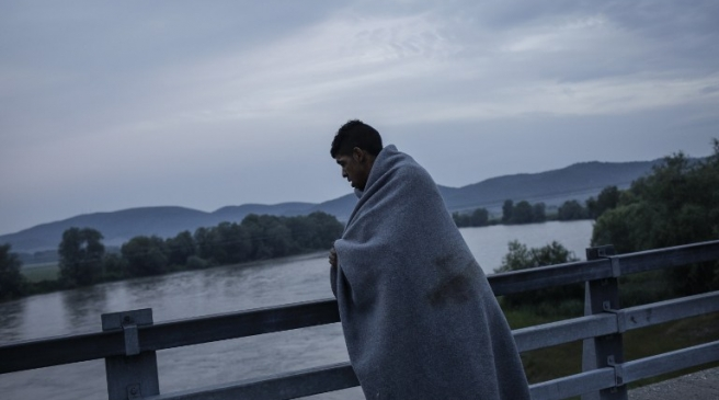 A man covered by a blanket crosses a bridge near Idomeni, Greece, 24 May 2016. Photo:Socrates Baltagiannis/dpa