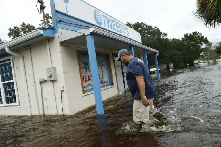 McCLELLANVILLE, SC - OCTOBER 8: John Tweedy wades into the swift-moving floodwater surrounding his business as he inspects damage in the wake of Hurricane Matthew on October 8, 2016 in McClellanville, South Carolina. Across the Southeast, Over 1.4 million people have lost power due to Hurricane Matthew which has been downgraded to a category 1 hurricane on Saturday morning. Brian Blanco/Getty Images/AFP