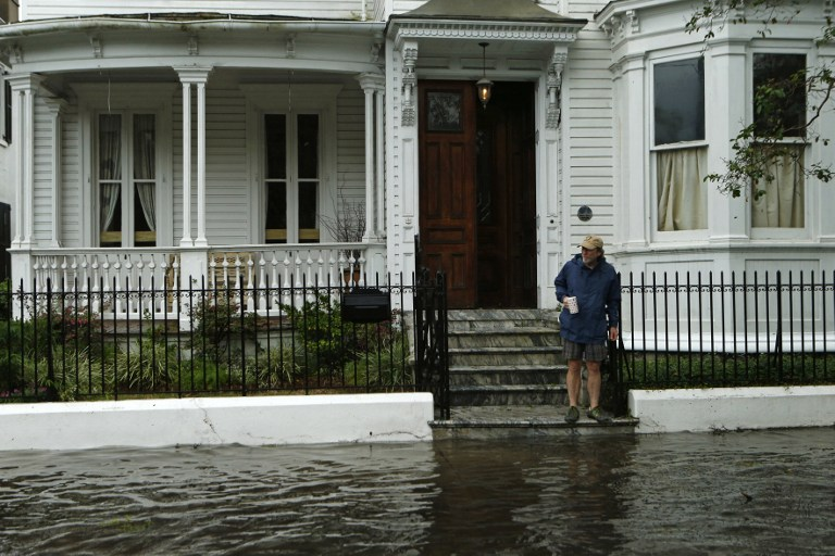 CHARLESTON, SC - OCTOBER 8: A resident stops short of the flooded sidewalk as he makes his way to the edge of the steps in front of a friend's home on Broad St. in the wake of Hurricane Matthew on October 8, 2016 in Charleston, South Carolina. Across the Southeast, Over 1.4 million people have lost power due to Hurricane Matthew which has been downgraded to a category 1 hurricane on Saturday morning. Brian Blanco/Getty Images/AFP