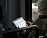 A lady views the RapidRide web site on an iPad connected to the free Wi-Fi on a B Line bus.