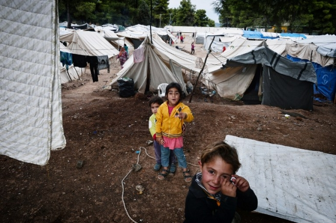 Children play inside the Ritsona refugee camp, north of Athens on October 21, 2016. The camp hosts some 500 refugees, mostly Syrian and Syrian-Kurd families living in tents and waiting to move to container houses. More than 60.000 refuges are stranded in Greece since the closure of the borders. / AFP PHOTO / LOUISA GOULIAMAKI