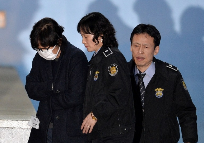 Choi Soon-Sil (L), the woman at the heart of a lurid political scandal engulfing South Korea's President Park Geun-Hye is escorted following her formal arrest, from the Central District Court in Seoul on November 3, 2016. A snowballing political scandal moved closer to embattled South Korean President Park Geun-Hye, with her newly nominated prime minister warning she could face a probe, hours after prosecutors detained a former presidential aide. / AFP PHOTO / KOREA POOL / KOREA POOL