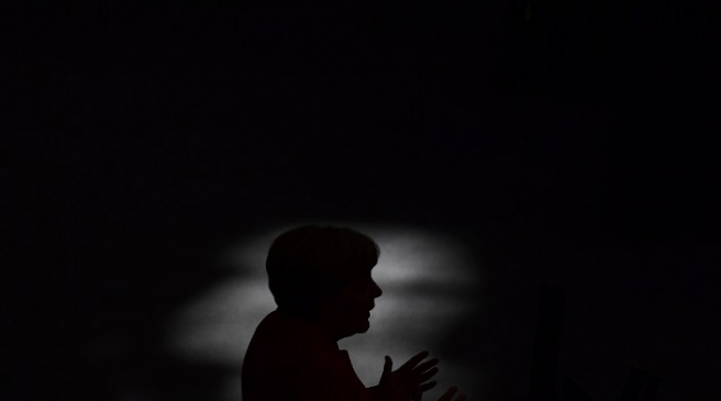 (FILES) This file photo taken on September 7, 2016 shows German Chancellor Angela Merkel being silhouetted as she gives a speech during a session of the German Bundestag (lower house of parliament) in Berlin. Merkel will stand for re-election as leader of the conservative Christian Democratic Union (CDU) party during the party's congress taking place from December 5 to 7, 2016 in Essen, western Germany. / AFP PHOTO / TOBIAS SCHWARZ
