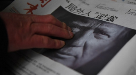 """(FILES) This file photo taken on November 10, 2016 shows a man buying a newspaper featuring a photo of US President-elect Donald Trump, the day after the US election, at a news stand in Beijing on November 10, 2016.   The headline reads """"Outsider strikes back"""".  President-elect Donald Trump broke with decades of cautious US diplomacy on December 2 to speak with the president of Taiwan, at the risk of provoking a serious rift with China. / AFP PHOTO / GREG BAKER"""