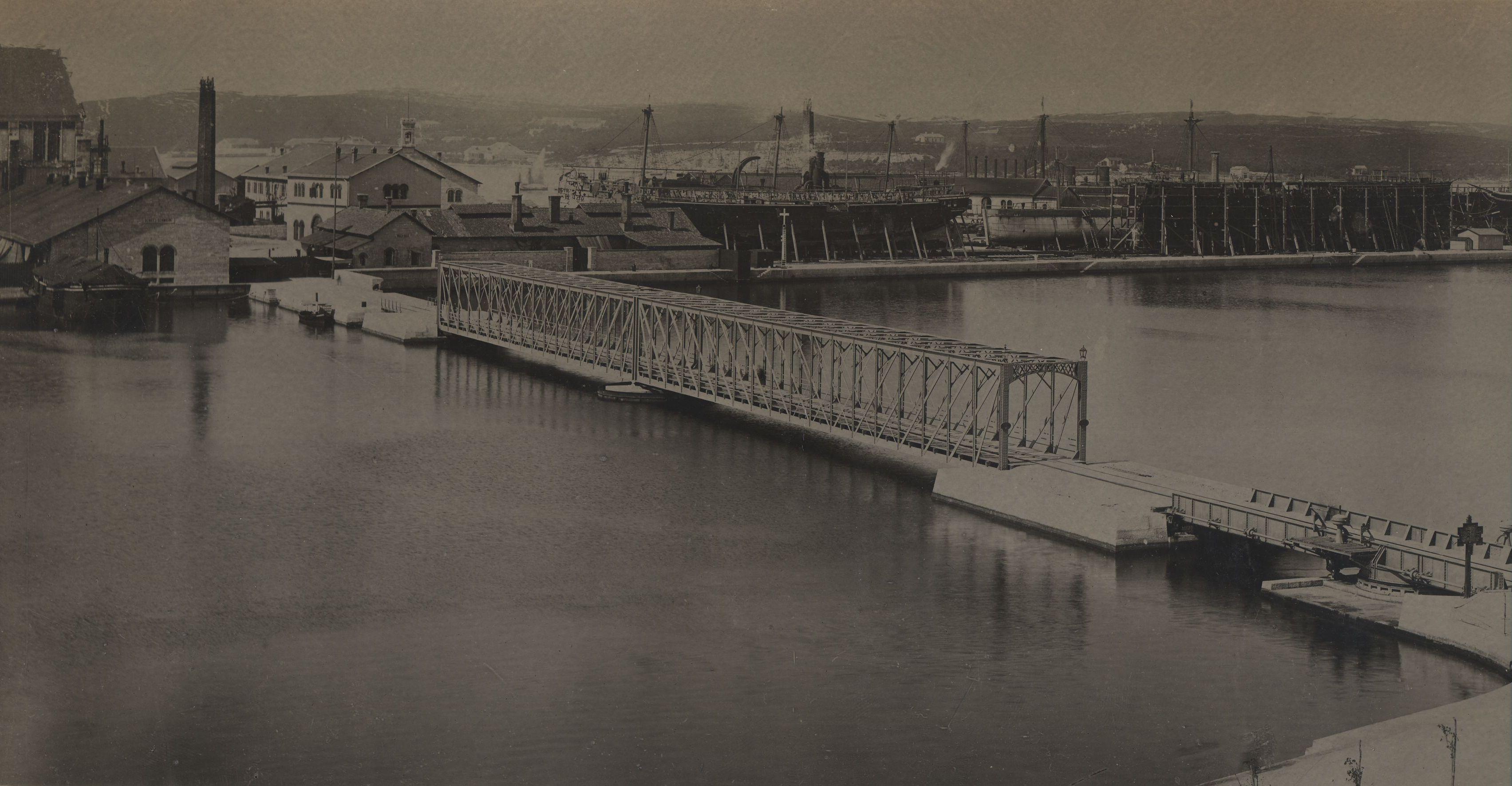 Na tom otočiću smješteni su bili tad, kao i danas, objekti i glavni pogoni brodogradilišta, a s obalom je povezan mostom. Na fotografiji je konstrukcija željeznog mosta od Rive prema brodogradilištu na otoku Uljanik, izgrađenog 1882. godine