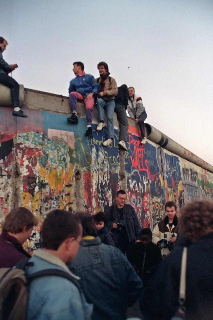 Mladi stanovnici Zapadnog Berlina sjede na zidu 16. listopada 1989. godine. Tjedan dana ranije, 9. listopada, vođa komunističke partije Gunter Schabowski dozvolio je stanovnicima Istočnog Berlina slobodno napuštanje države, bez ikakve posebne dozvole.