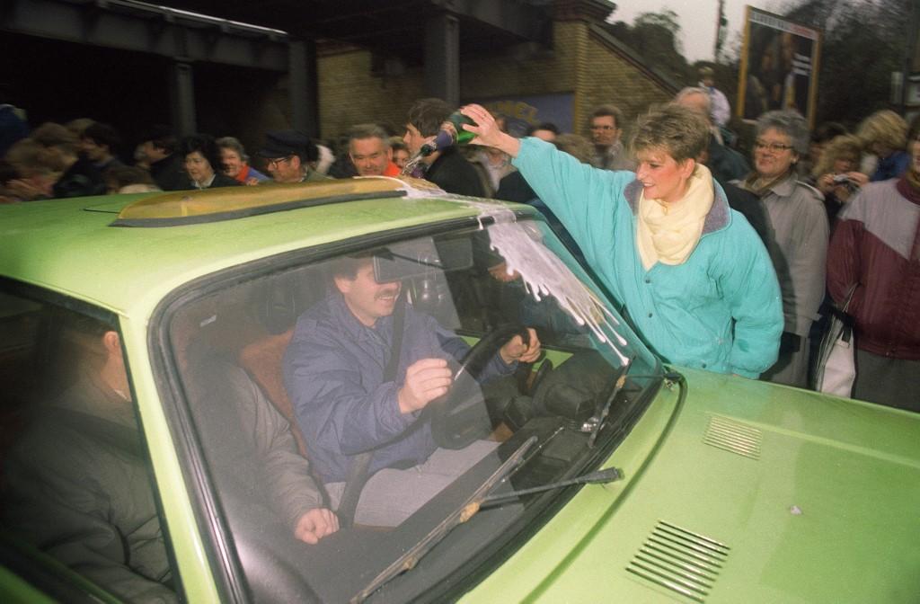 Žena iz Istočnog Berlina polijeva šampanjac po automobilu čovjeka iz Zapadnog Berlina, čime mu, očito, želi dobrodošlicu.